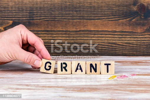 Grant. Wooden letters on the office desk, informative and communication background