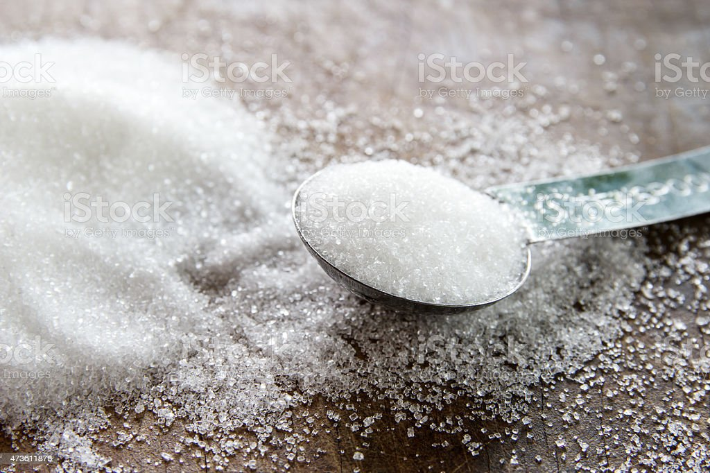 granulated sugar in spoon and sugar pile on wooden stock photo