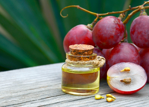 Grape seed oil in a glass jar and fresh grapes on old wooden table in the garden.Spa,bodycare,Bio,Eco products concept. Selective focus.