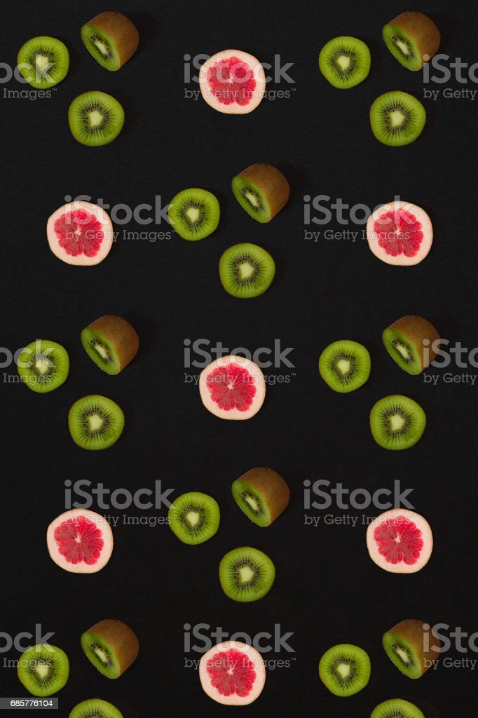Grapefruit and kiwi pattern on black background. Minimal flat lay concept royalty-free stock photo