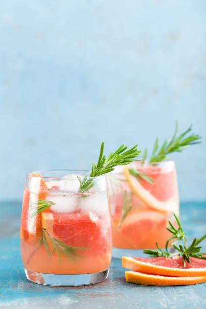 cocktail, boisson avec de la glace rafraîchissante au gin pamplemousse et romarin - infusion pamplemousse photos et images de collection