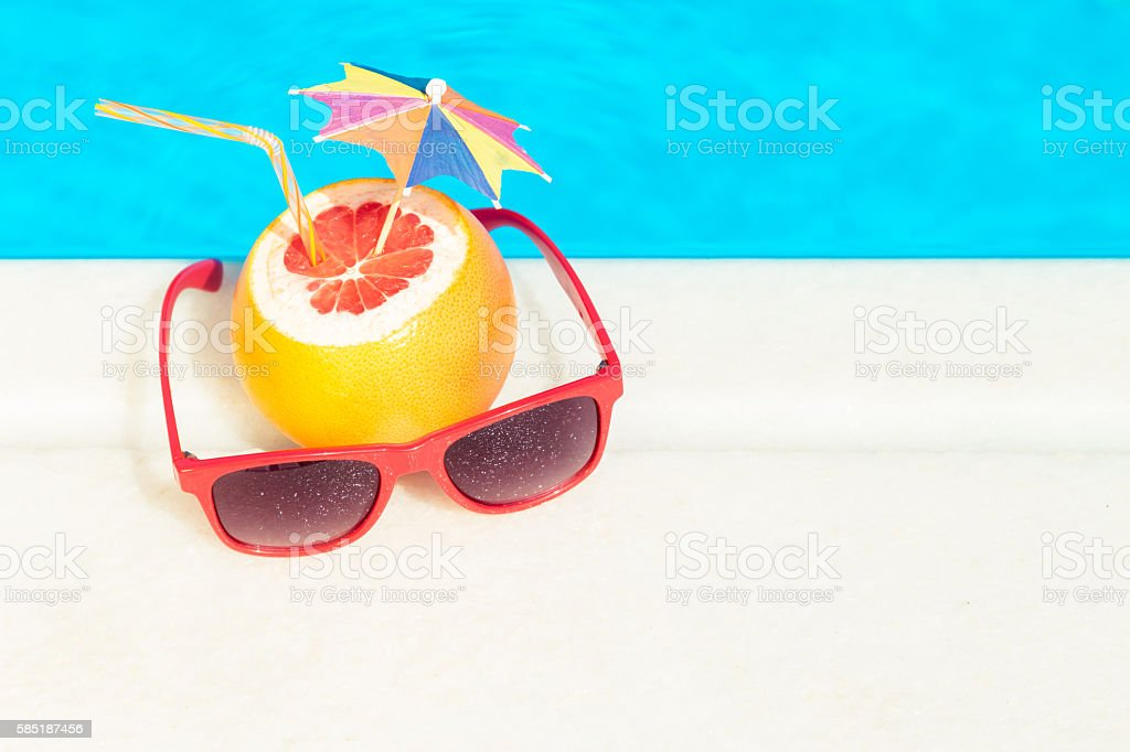 Grapefruit and sunglasses at the edge of swimming pool stock photo