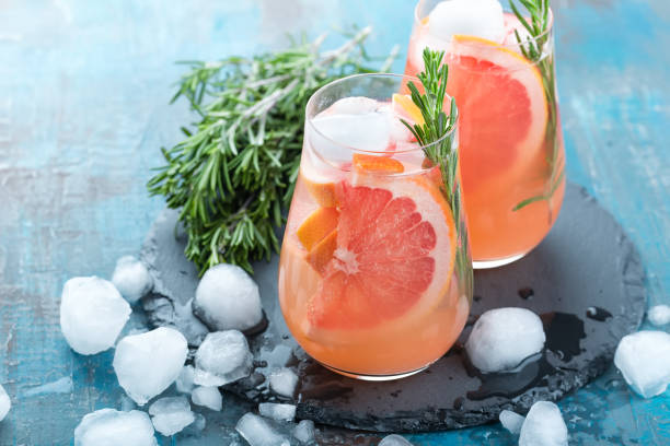 grapefruit and thyme gin cocktail, refreshing drink with ice - grapefruit cocktail stock photos and pictures