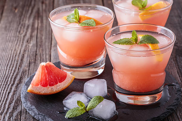 grapefruit cocktail with ice and mint. - grapefruit cocktail stock photos and pictures