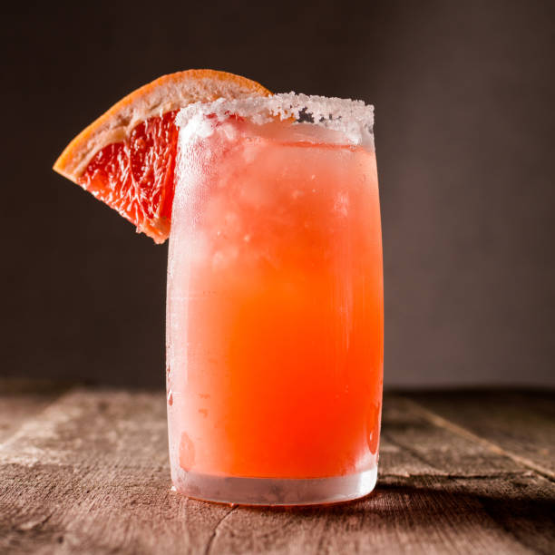 Grapefruit cocktail with ice and salt on a wooden background. Party time. square
