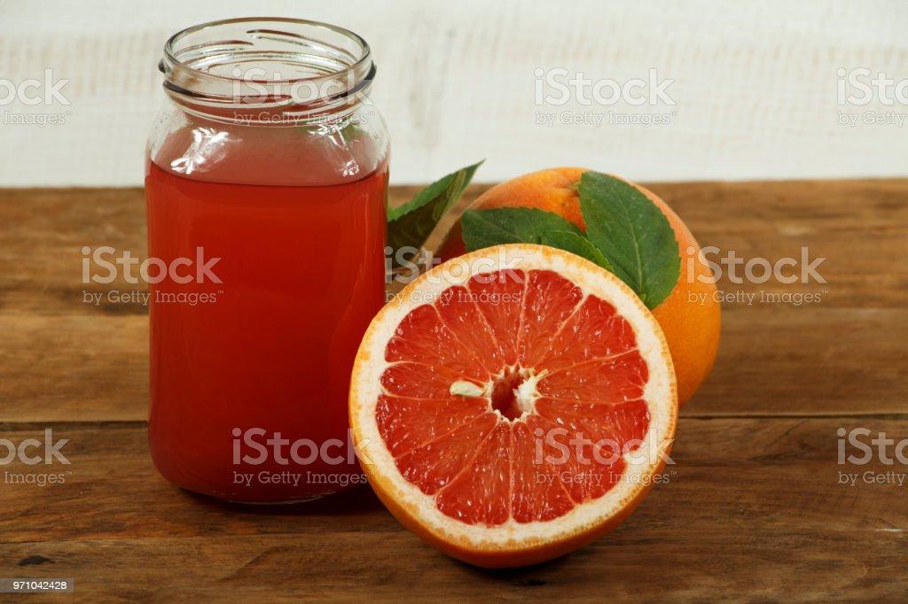 Grapefruit juice and fresh grapefruit on a wooden background. Fresh...