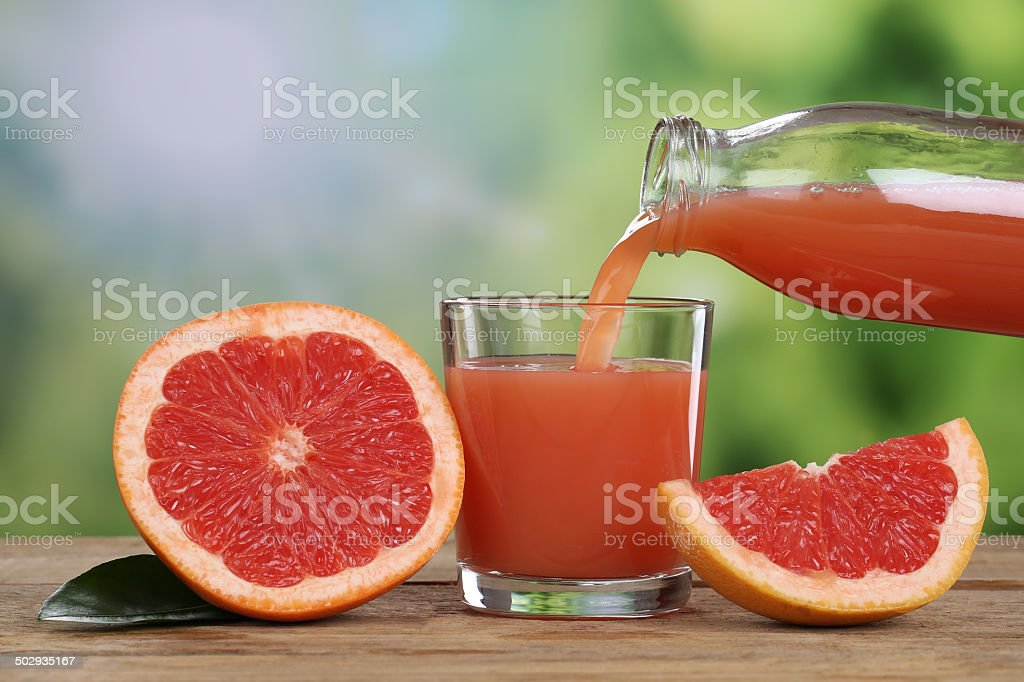 Grapefruit juice pouring into a glass stock photo