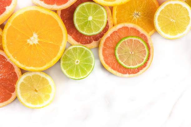 Grapefruit, lime, lemon, and orange slices with copyspace Vibrant juicy citrus fruits on a white marble texture with copy space. Grapefruit, lime, lemon, and orange slices acid stock pictures, royalty-free photos & images