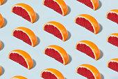 Fruit pattern with half slices of grapefruit on soft blue pastel background