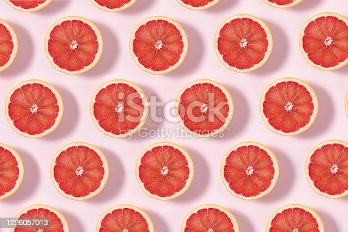 Grapefruit slices in a row on pink background
