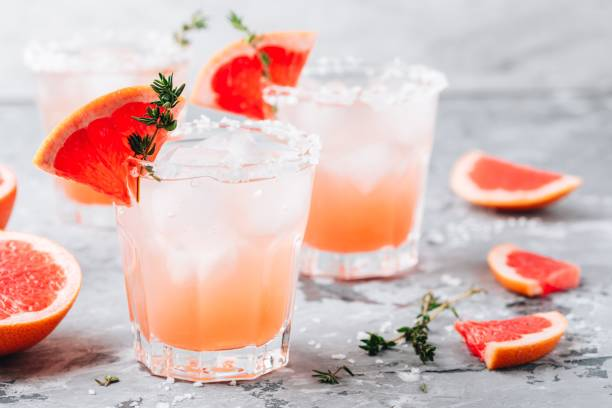 Grapefruit salty dog Cocktail Grapefruit salty dog Cocktail with ice in glass on gray stone background tequila shot stock pictures, royalty-free photos & images