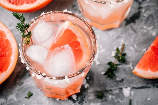 Grapefruit salty dog Cocktail Grapefruit salty dog Cocktail with ice in glass on gray stone background mule stock pictures, royalty-free photos & images
