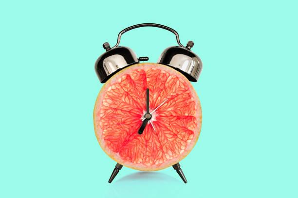 Grapefruit Scheibe auf Wecker, blauer Pastell-Hintergrund. Obst-und Vitamindiät beim Frühstücks-Ernährungskonzept – Foto