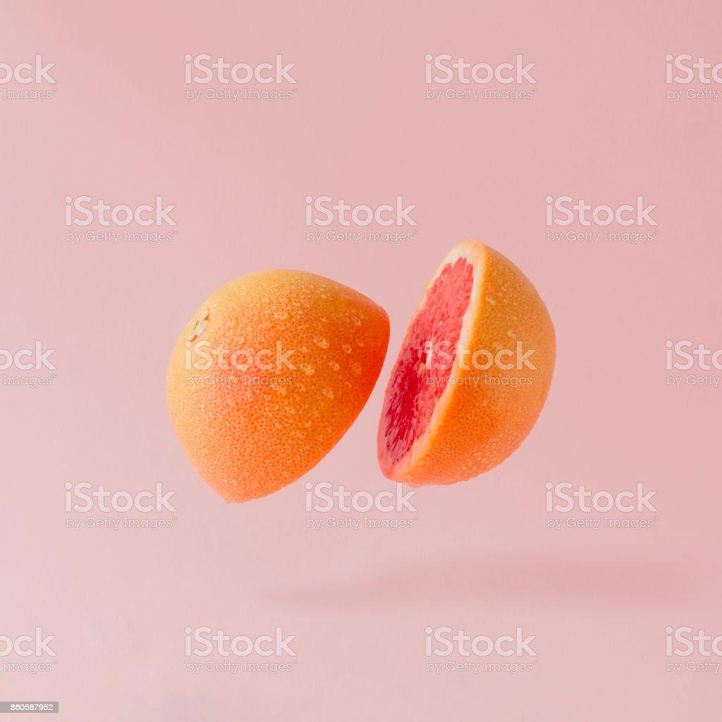 Tranches de pamplemousse sur fond rose pastel. Concept fruits minime. - Photo