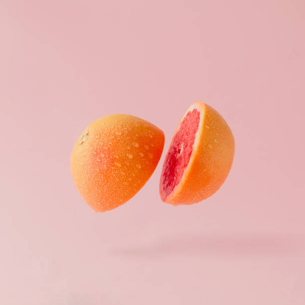 Grapefruit sliced on pastel pink background. Minimal fruit concept. stock photo