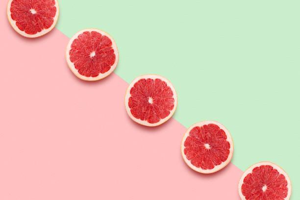 Grapefruit Scheiben in Reihe auf pastellrosa und grünen Hintergrund. Minimales Sommerkonzept Flat lay. – Foto
