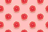 Grapefruit slices tropical seamless pattern on pink background Minimal summer concept. Flat lay, trendy juicy color.