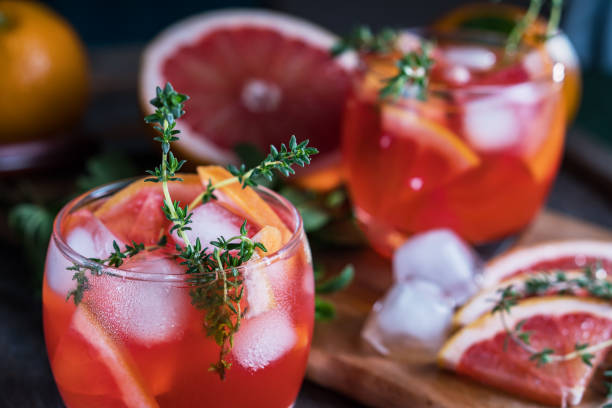 Grapefruit, thyme and ice cocktail. Refreshing drink on rustic background, close-up. stock photo