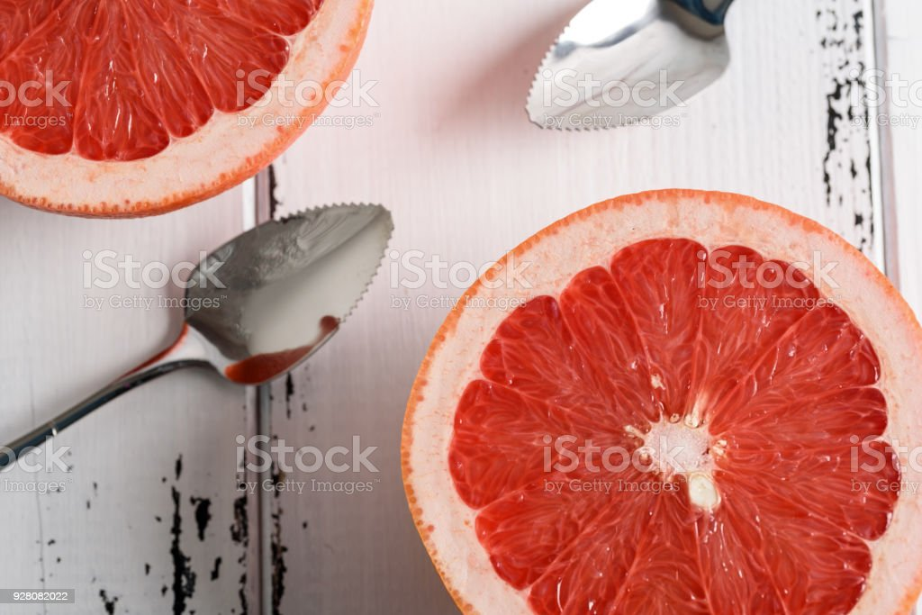 Grapefruit with spoon on white wooden background stock photo