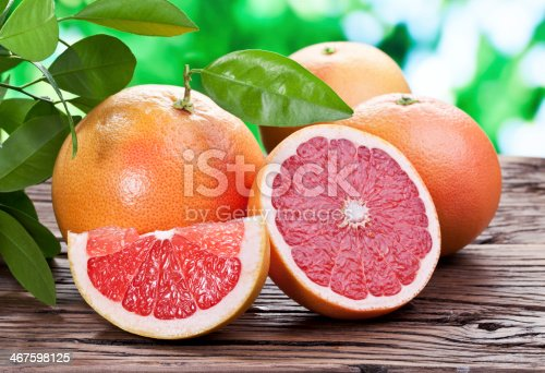 Grapefruits on a wooden table with green foliage on the background.
