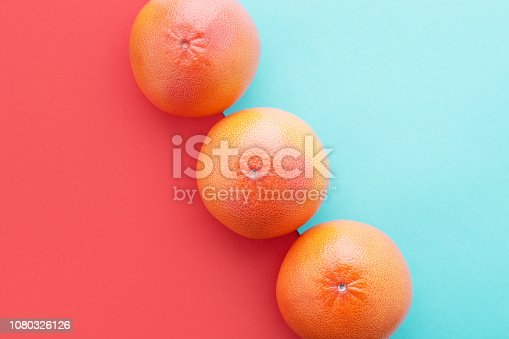 istock Grapefruits on Living Coral & pastel blue color diagonal background Minimal summer. 1080326126