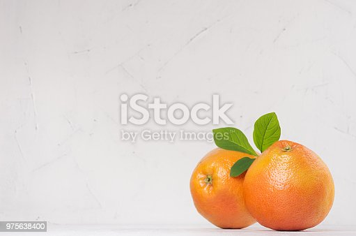 istock Grapefruits with green leaves on white wood board with copy space. 975638400