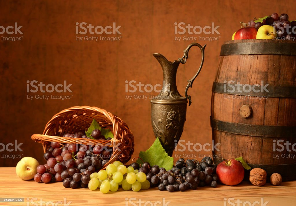 Grapes, a metal pitcher and barrel on wood table stock photo