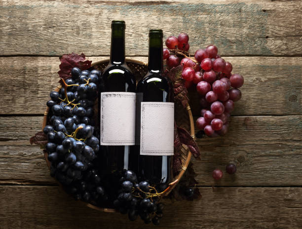 Grapes and bottles of red wine. Old empty paper labels , copy space for your text. stock photo