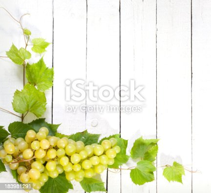 istock Grapes and leaves on vintage white planks background 183981291