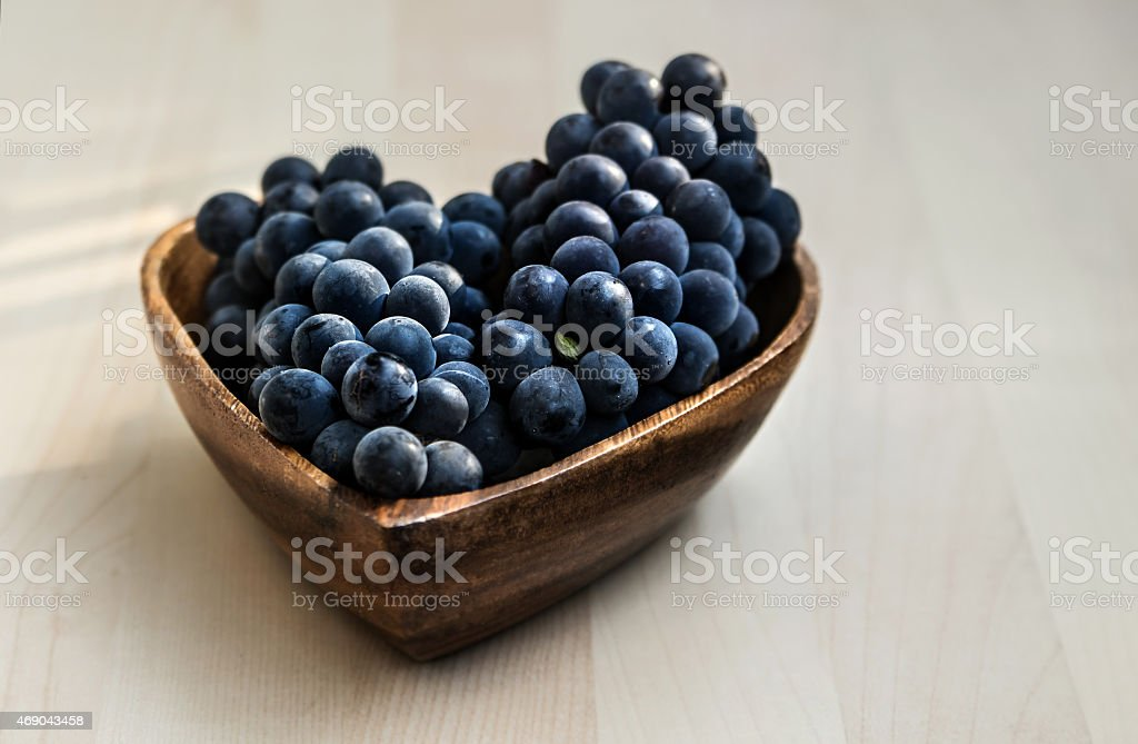Grapes in a heart shape wooden plate stock photo
