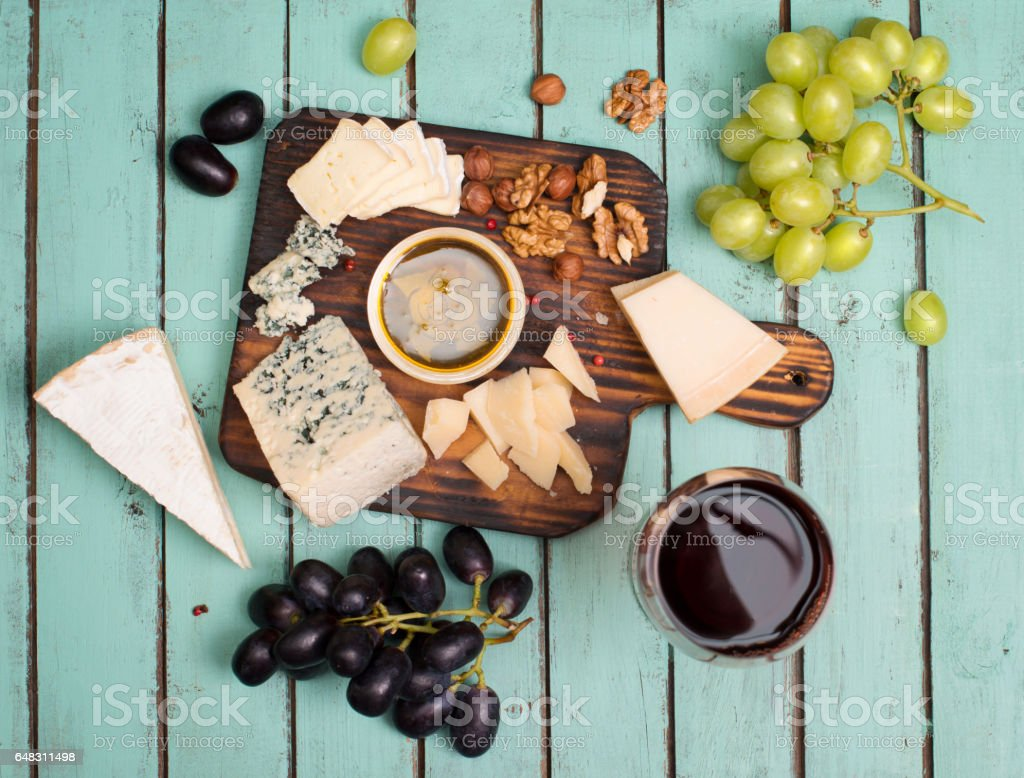 Grapes, red wine, cheeses, honey and nuts over shabby wood. stock photo