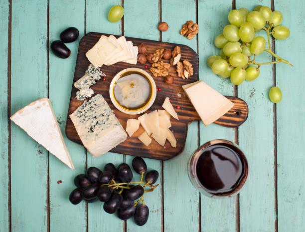 Trauben, Rotwein, Käse, Honig und Nüssen über schäbige Holz. – Foto