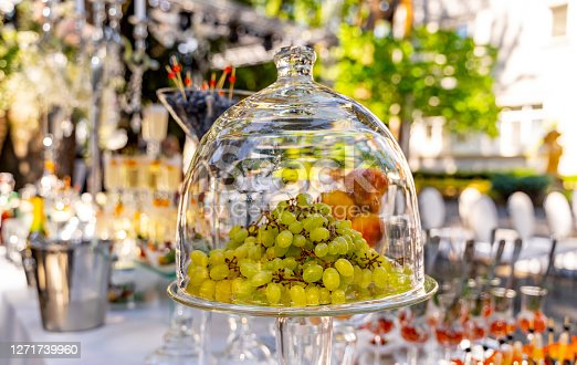 Grapes under glass transparent dome cover. Dessert on the festive table. Wedding table decoration. Selective focus.