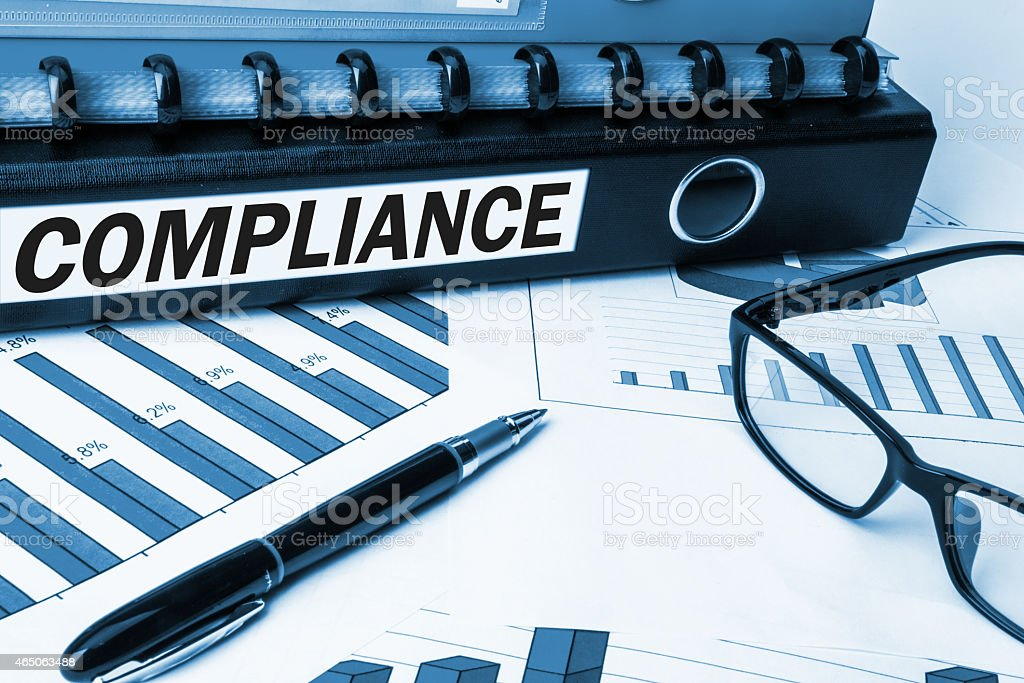 Graph documents with a pen and a binder labeled compliance stock photo