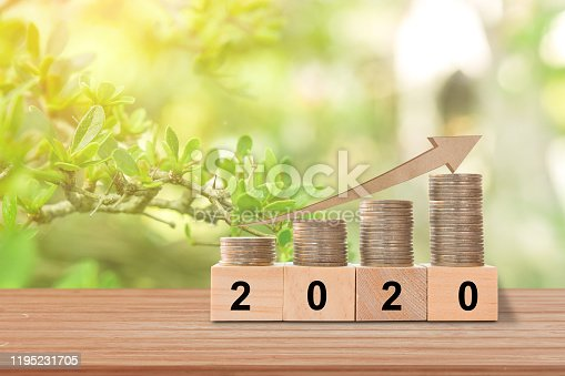 1039640896 istock photo Graph of coins economics growth on wood cubes. Concept success in 2020 year. copy space. 1195231705