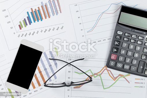 863469700 istock photo graph with glasses, smartphone, and calculator on stock market report as background 1013490050
