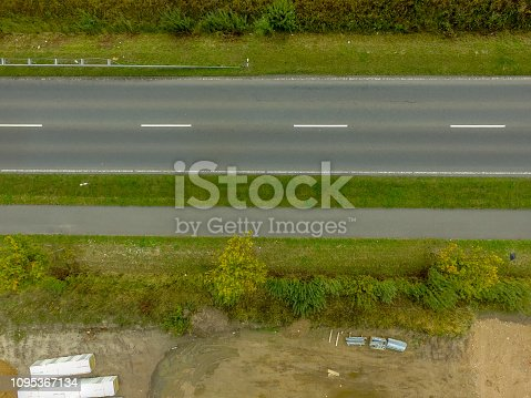 1095367134 istock photo Graphic and abstract aerial view of the vertical photograph of a road with markings between fields. 1095367134