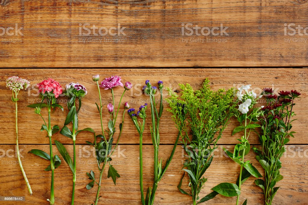 graphic arrangement of wild flowers on wooden table stock photo
