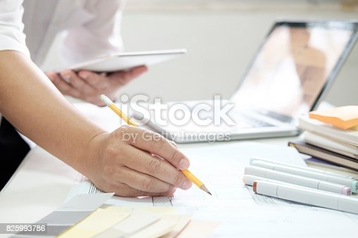istock Graphic design and color swatches and pens on a desk. Architectural drawing with work tools and accessories. 825993786