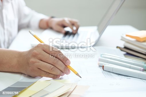 istock Graphic design and color swatches and pens on a desk. Architectural drawing with work tools and accessories. 825993788
