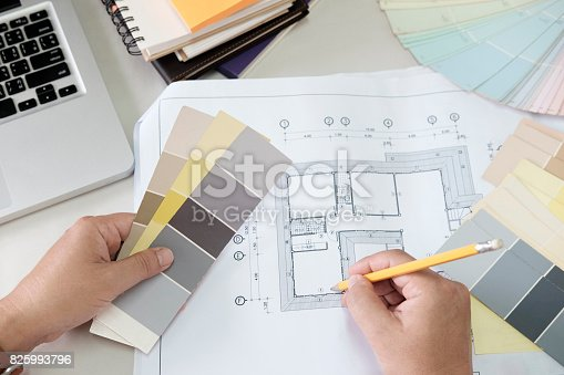 istock Graphic design and color swatches and pens on a desk. Architectural drawing with work tools and accessories. 825993796