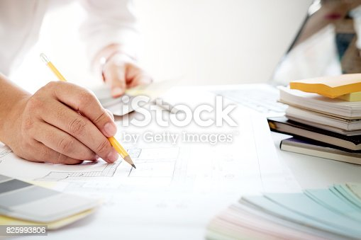 istock Graphic design and color swatches and pens on a desk. Architectural drawing with work tools and accessories. 825993806
