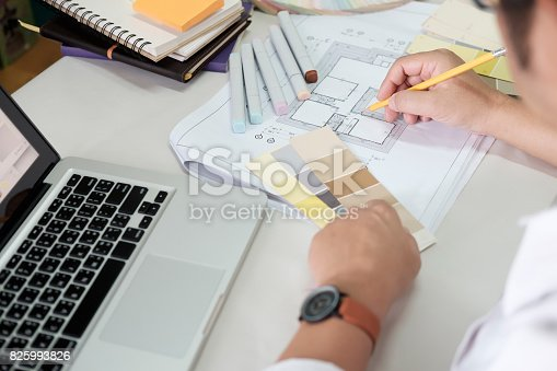 istock Graphic design and color swatches and pens on a desk. Architectural drawing with work tools and accessories. 825993826