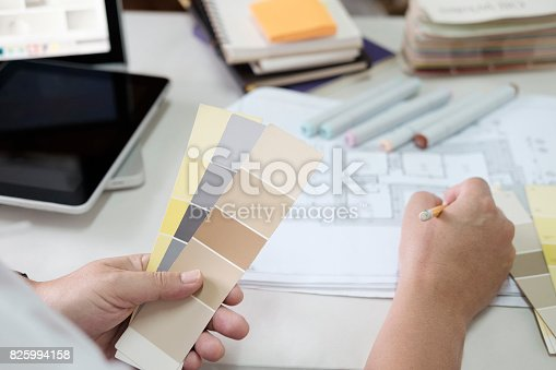 istock Graphic design and color swatches and pens on a desk. Architectural drawing with work tools and accessories. 825994158