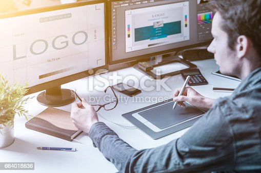 Computer graphic designer designs logos and advertising graphics. Draws a logo on the graphics tablet.