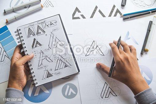 istock Graphic designer drawing sketch design creative Ideas draft Logo product trademark label brand artwork. Graphic designer studio Concept. 1162153149