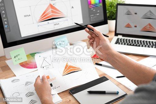 istock Graphic designer drawing sketches logo design. 1280956265