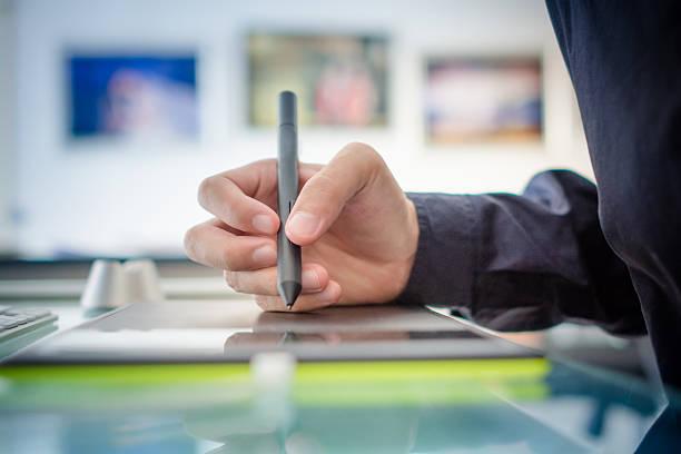 Graphic designer mano utilizzando digitale tablet pen - foto stock