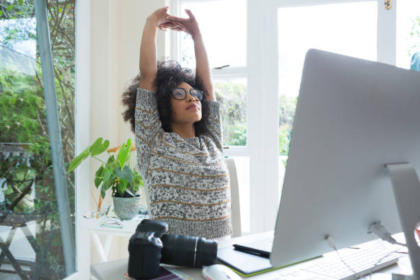 Graphic designer stretching her arms stock photo