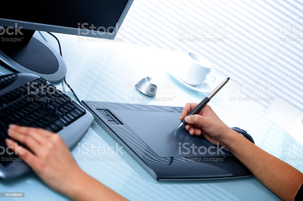 Graphic designer using digital tablet and computer in the office royalty-free stock photo